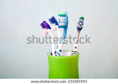 Toothbrushes in glass on table - stock photo
