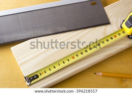 Toothed steel hand saw cutting through a new boards of wood left in position surrounded by wood chips with nobody in the frame in a DIY, carpentry, woodworking or joinery concept - stock photo