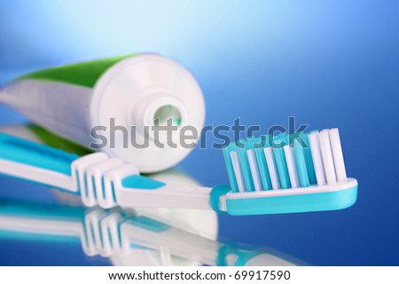 toothpaste and brush on a blue background - stock photo