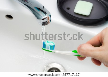 Toothpaste on the toothbrush in hand, in the bathroom sink. - stock photo