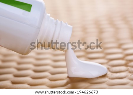 Toothpaste squeezed from tube, close-up, on bright background - stock photo