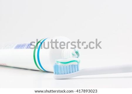 toothpaste tube with a small amount of toothpaste on a toothbrush - stock photo