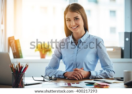 Toothy smile from real expertise. Cheerful young beautiful woman looking at camera with smile while sitting at her working place - stock photo