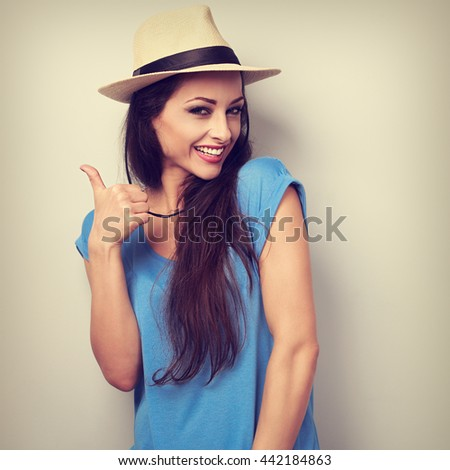 Toothy smiling young woman in summer hat showing thumb up sign. Toned closeup portrait - stock photo