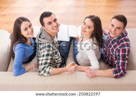 Top and back view of a four young people, students are sitting on sofa with book and looking at the camera. - stock photo