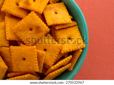 Top close view of a bowl of cheese crackers atop an orange background illuminated with natural light. - stock photo