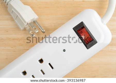 Top close view of a household surge protector on a wood table top. - stock photo