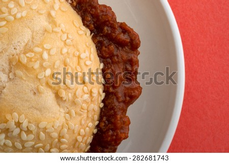 Top close view of a sloppy joe sesame seed roll sandwich on a small plate atop an orange table top. - stock photo