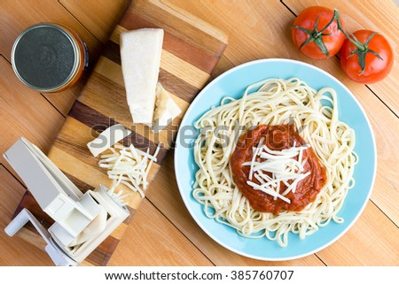 Top down first person perspective view on blue plate of noodles topped with red sauce and grated gruyere cheese next to pasta press and medium tomatoes - stock photo