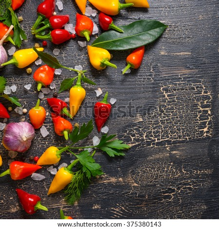 top down of yellow, red hot chili peppers, sea salt, greenery, black peppers and garlic on cracks black background, close up - stock photo