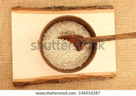 Top Down View Of A Bowl Of Steel Cut Oatmeal On Wooden Plank - stock photo