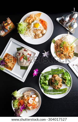 Top down view of a variety of authentic Thai and stir fry dishes.  Shallow depth of field. - stock photo