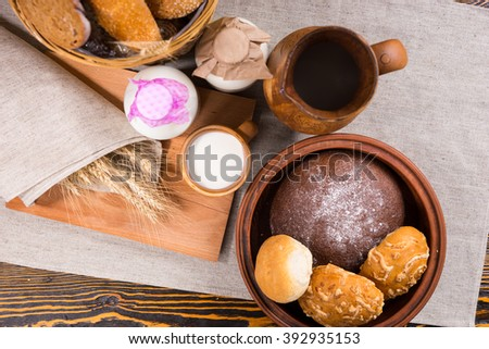 Top down view of breads in a basket and bowl by two glass bottles and a mug of milk and a wooden jug beside wheat grains wrapped in linen - stock photo