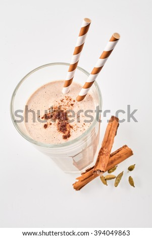 Top down view of delicious cinnamon smoothie garnished with cardomom beside herbs with two matching straws over white background - stock photo