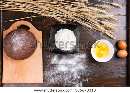 Top down view on baking ingredients of eggs, yolks, fine white flour, stalks of dried wheat and rye roll on top of cutting board - stock photo