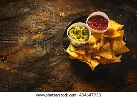 Top down view on delicious crunchy appetizer of triangular yellow corn tortilla chips beside little bowls of guacamole and salsa dip over old dark wooden table with copy space - stock photo