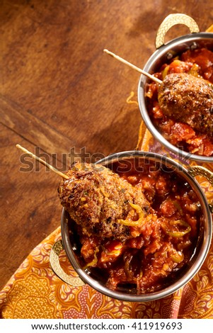 Top down view on Indian style cuisine of ground meat rolls with skewers dipped in hot sauce over decorative table cloth - stock photo