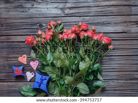 Top down view on large bundle of pink roses, Valentines Day hearts and two diamond shaped gift boxes over weathered wooden background - stock photo