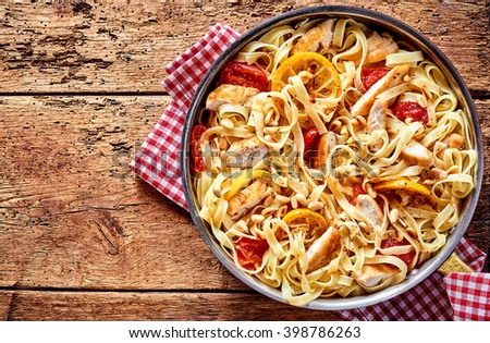 Top down view on round steel pan full of freshly cooked tomatoes, lemon slices, chicken meat and pasta noodles over rustic table background with copy space - stock photo
