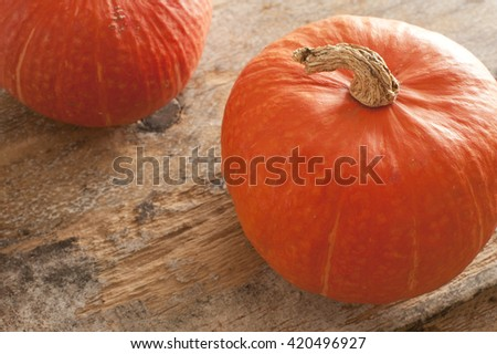 Top down view on two orange pumpkins with dried up stem over old weathered wooden table - stock photo