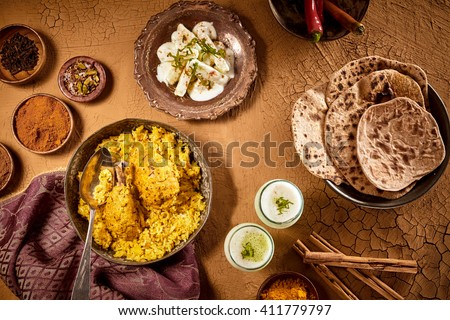 Top down view over table with Indian culinary dishes of curried chicken biryani with bread and sauces - stock photo