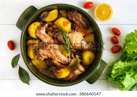 Top flat view of roasted rabbit meat with vegetables and herbs  in round ceramic pot on white wooden table surface - stock photo