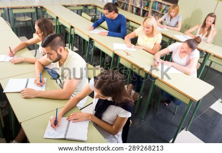 Top group shot of students in classroom writing dictation in their copybooks - stock photo