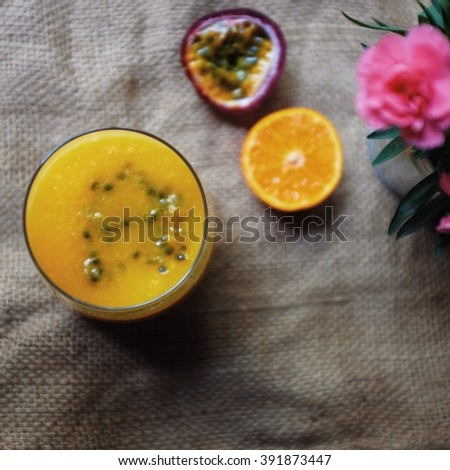 Top look of colorful smoothie; mango orange and passion fruit. Selective focus on smoothie glass. - stock photo