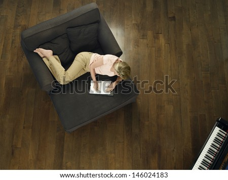 Top of a middle aged woman writing in notebook on sofa at home - stock photo