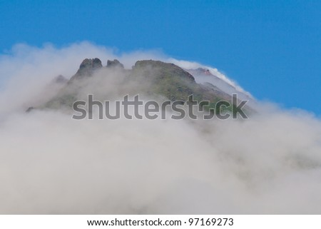 Top of Arenal Volcano reaching above clouds, rainy season, Costa Rica - stock photo