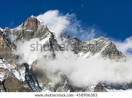 top of Lhotse and Nuptse with clouds on the top - way to mount Everest base camp, Khumbu valley, Sagarmatha national park, Nepalese Himalayas - stock photo