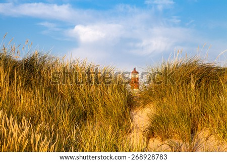 Top of lignthouse is seen behind sand dune covered with grass and on blue sky background with clouds.The lighthouse is located on Baltic sea coast in Liepaja, Latvia. The foreground is in focus - stock photo