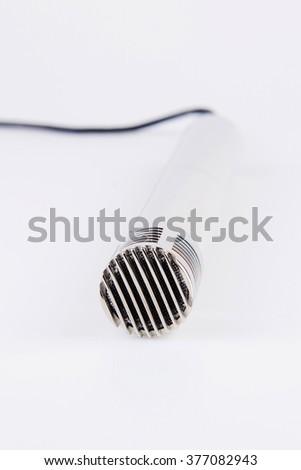 top of metallic microphone on white - stock photo