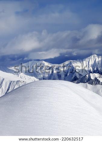 Top of off piste snowy slope and cloudy mountains. Caucasus Mountains, Georgia, ski resort Gudauri. - stock photo