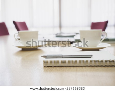 Top of table with coffee and book with Blurred conference room interior background - stock photo