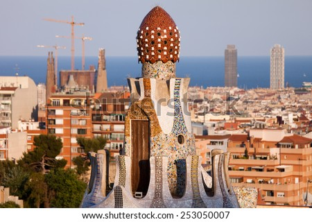 Top of the Casa del Guarda by Antoni Gaudi in Park Guell against Barcelona skyline in Catalonia, Spain. - stock photo