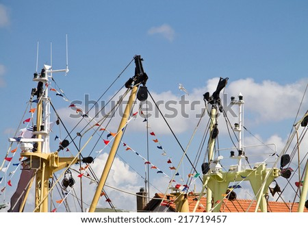 Top of the masts of a ship in the harbor - stock photo