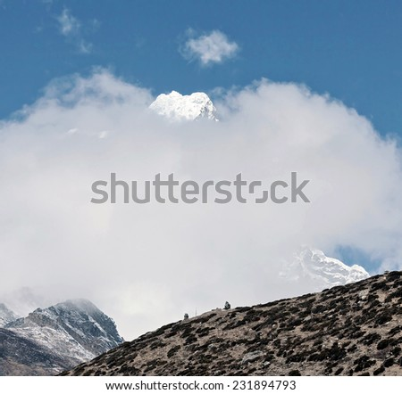 Top of the Tabuche peak in the clouds from the village of Dingboche in the valley of Chhukhung district Everest - Nepal, Himalayas - stock photo