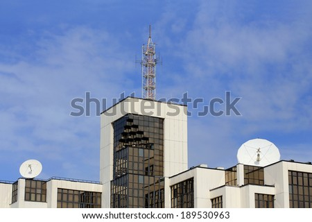 Top of the tech building with glass walls and radio equipment on the roof - stock photo