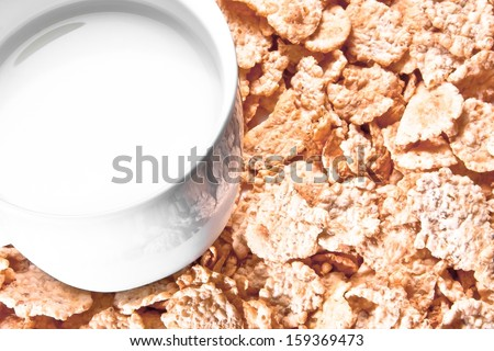 top of view of cup of milk on corn flakes background - stock photo