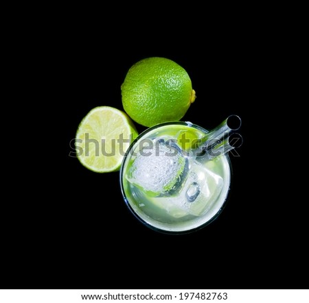 top of view of glasses with cocktail and ice near lime on black background, disco club atmosphere - stock photo
