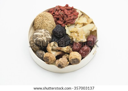 Top on assortment of Chinese herbal soup ingredients consist of dried mushroom, herbal roots, dried dates and berries in a bamboo bowl.  Isolated on white background. - stock photo