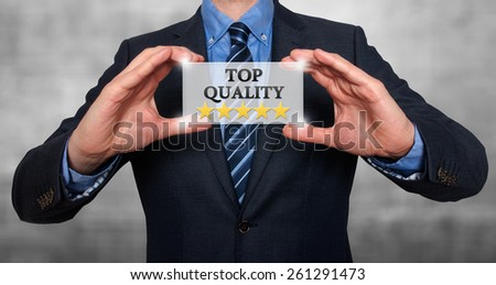 TOP Quality with five stars - Businessman with sign - Grey - Stock Photo - stock photo