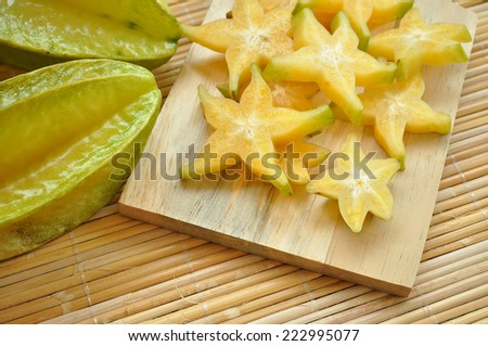 Top shot of starfruit and its slices on a wooden chopping board - stock photo