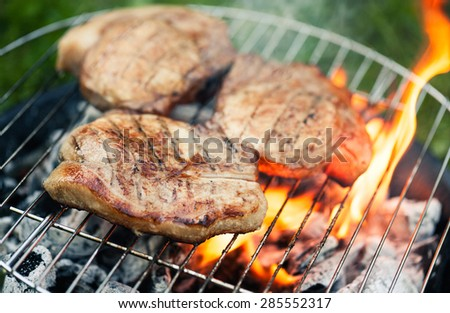 Top sirloin steak on a barbecue, shallow depth of field. Summer BBQ closeup, outdoor grill concept. Grilled steak meat cooked on carocal.  - stock photo