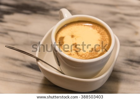 Top view a cup of Giang egg coffee in Hanoi on marble table. Since 1946 the coffee is dripped and brewed in a small cup with filter then addition of well-whisked mixture yolks and other ingredients. - stock photo