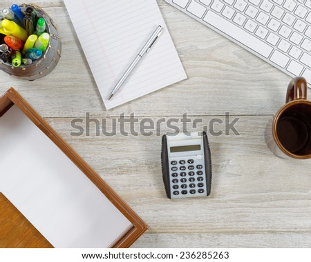 Top view angle shot of home office wooden desktop with various items including: keyboard, inbox, envelopes, coffee mug, note pad, pen, pencil and pen cup holder, and calculator.  - stock photo