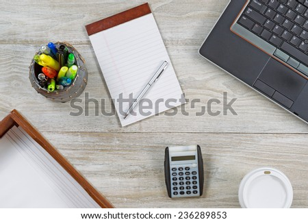 Top view angle shot of home office wooden desktop with various items including: laptop, keyboard, inbox, envelopes, coffee paper cup, note pad, pen, pencil and pen cup holder, and calculator.  - stock photo