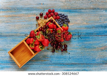 Top view appetizing bright ripe berries lay in a wooden form, they abound in vitamins and oxidants are beneficial for the whole body, energize the whole day - stock photo