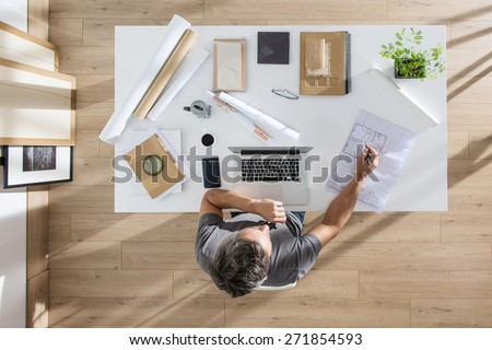 top view, architect sitting at  desk and working on his laptop, there is blueprints and model house on his table, the sun casts graphics shadows on the wood floor - stock photo